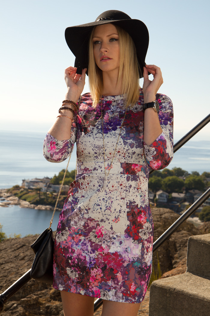 Vancouver Fashion Blogger, Alison Hutchinson, wearing H&M pink and purple floral dress, Zara black wide-brimmed hat, H&M black leather cross-body bag, Zara high heel boots, True Worth Design crystal pendant