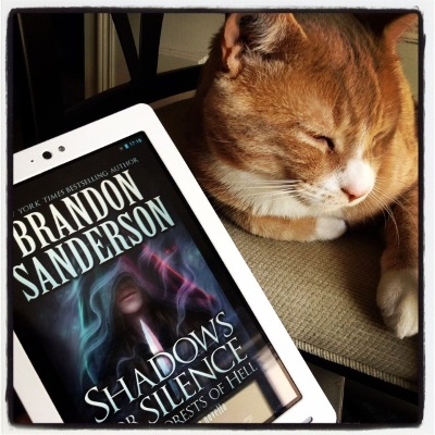 A ginger cat, Ollie, lounges on a buff bar stool, his eyes almost closed and one paw extended. In front of him is a white Kobo with the cover of Shadows For Silence in the Forests of Hell on its screen. The cover features a white woman with her hood pulled down over her eyes. She holds a dagger in front of her while indistinct spirits, most with green eyes but one with red, swirl around her.