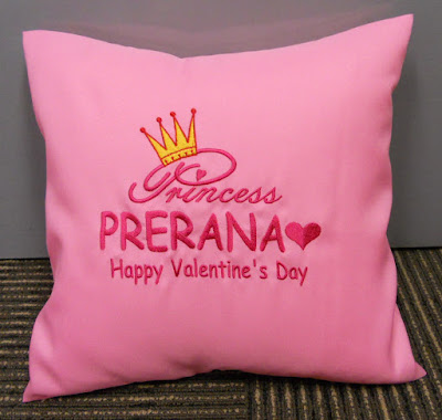 Pink cushion with embroidery on it.
