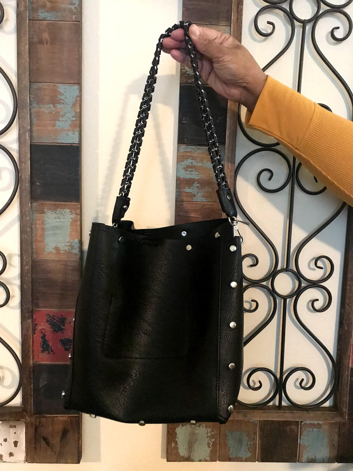 Image: Woman holding handbag that may be donated as part of decluttering and organizing her things