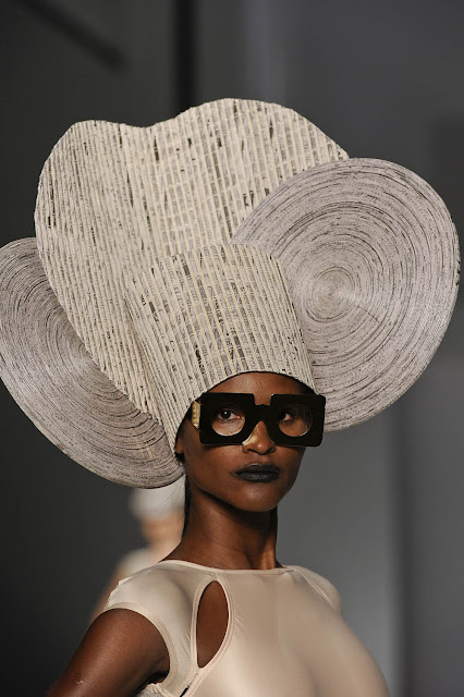 large hat made of rolled newspaper on model