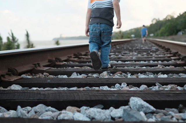 baby walking on train tracks