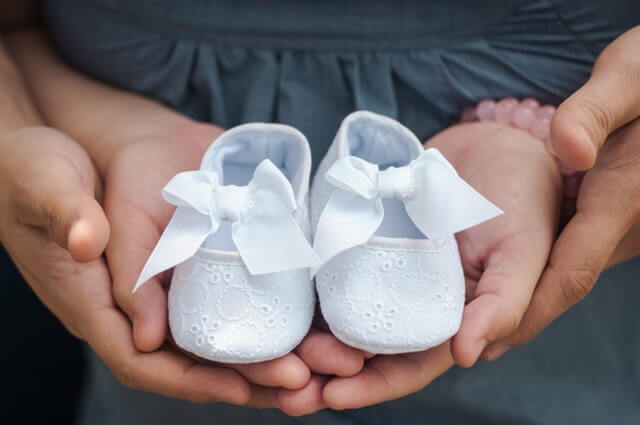 Person Carrying Pair of Baby's White Flats HD Copyright Free Image