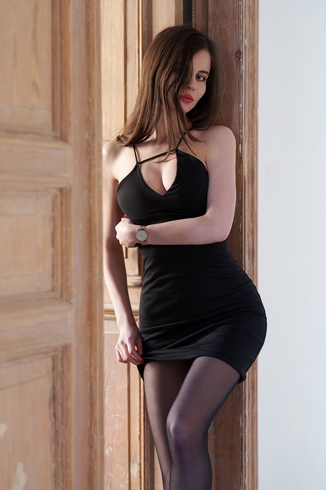 Czarna sukienka z oryginalnym dekoltem, czarne rajstopy i złoty zegarek