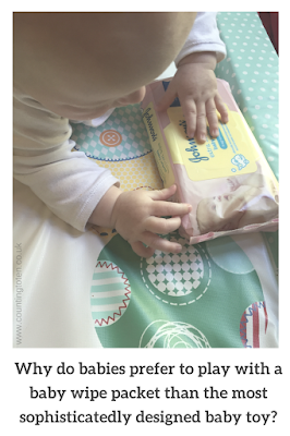 A baby on a changing mat playing with a packet of Johnson's Baby Wipes