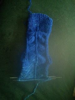 A knit sock laying flat.  The heel is tucked behind, and the colour is transitioning from a royal blue at the cuff to a sky blue past the heel. The foot is not complete, the stitches are live on dpns.