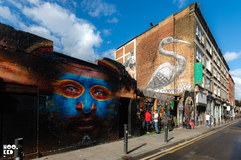 Artist Dale Grimshaw street art mural with work by artist Roa in the background