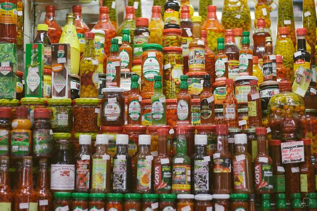 uma parede de potes de pimenta fazem a decoração de uma pequena loja do mercado central