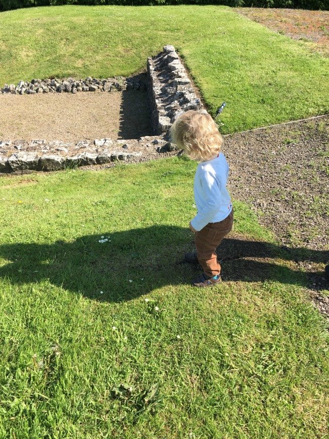 toddler-on-grass-next-to-ruins-with-two-shadows