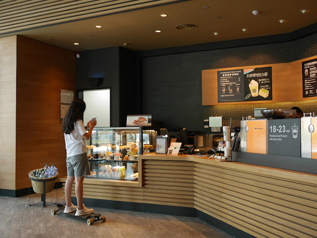 young woman on skateboard at a Starbucks counter