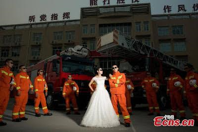 Fire-fighter poses for unconventional wedding photos with his partner.