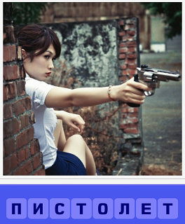 за кирпичной стенкой сидит женщина с пистолетом