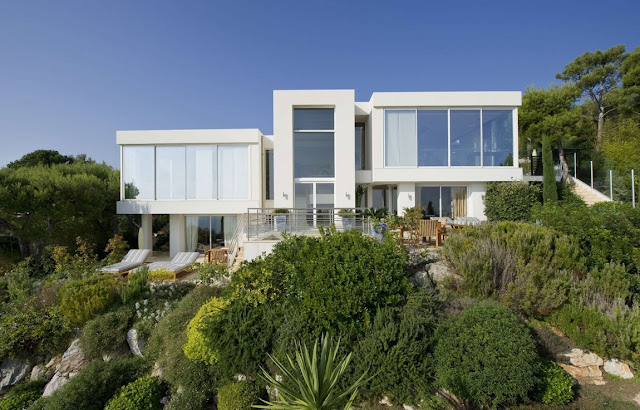 Modern white two story villa built among green vegetation