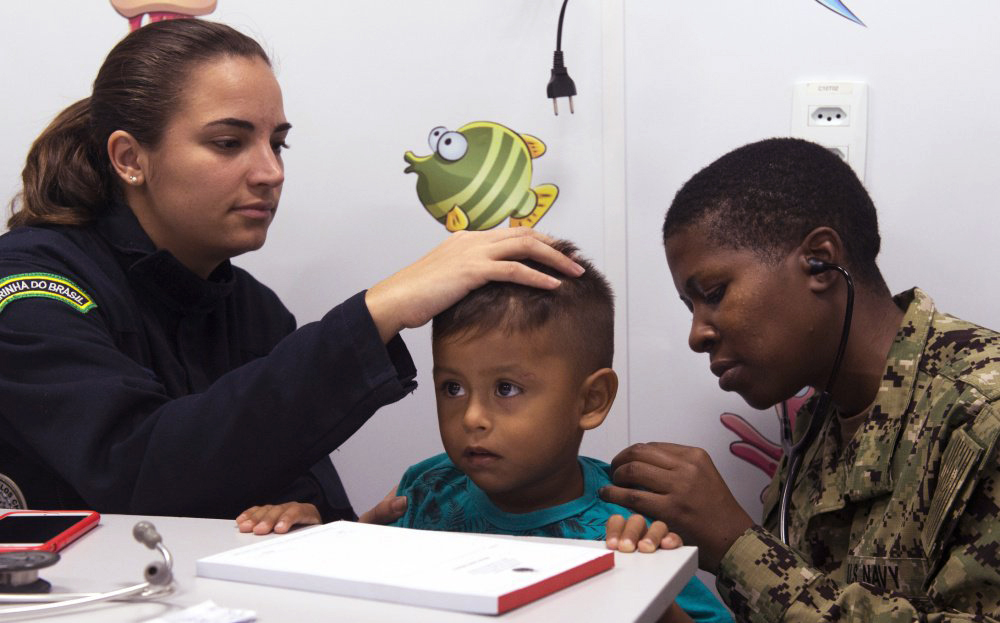 Two military doctors perform a checkup on a child