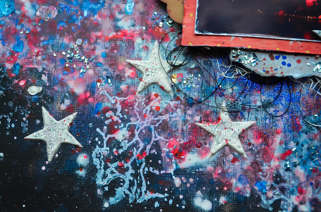 Scrap Our Stash Design Team Independence Day Fourth of July Fireworks Red white and blue, black Bazzill background mixed media with texture paste, acrylics, glimmer mists, and stenciling with chipboard stars using encrusted jewel technique