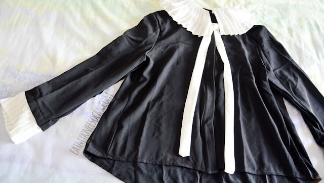 Details on the ruffled pleated black-and-white self-tie long sleeve button down blouse from Twist X Turn.