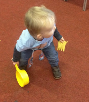 Toddler holding toy saucepan and fries and crouching