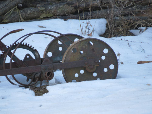 old rusted farm machinery and gears against the snow