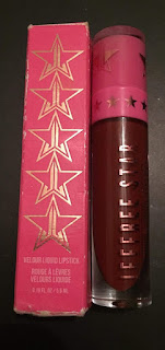 A cylindrical glass bottle containing a dark red liquid with a pink handle next to a pink rectangle box with jeffree star in silver font on a bright background.