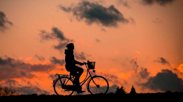 samotna dziewczyna jedzie przez pole