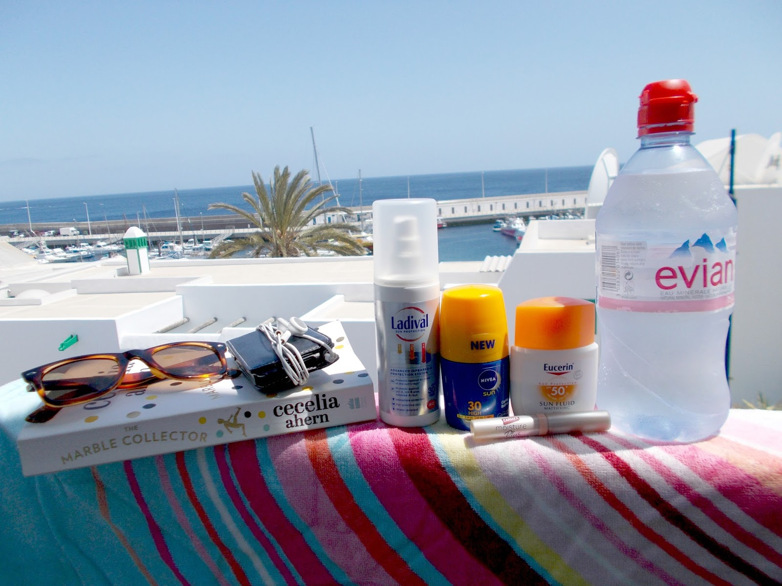poolside beach side vacation holiday essentials sunscreen ladival spf eucerin mattifying fluid nivea caring roll on carmex moisture plus lip balm sunglasses water book ipod beach towell bag