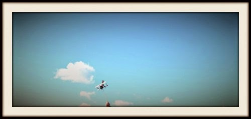 Avión de cartón sujetado por un niño y de fondo el cielo
