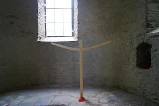 Ein geschwungenes Kreuz steht auf zerstörtem Boden unterhalb der Kirchenfenster