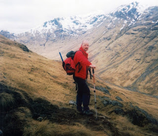 A man on a hillside with more snow-covered hills in the background