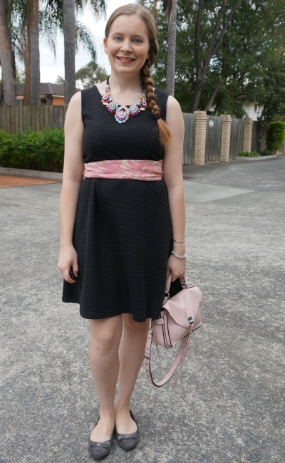 black fit and flare sleeveless dress with pink accessories statement necklace scarf as belt peony darren bag | away from blue