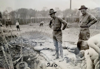 A black and white photograph of two men in uniform overseeing a trench.
