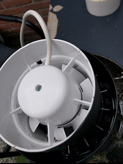 The fan attached to the (upside-down) chimney top. Note the two bolts that just allow the fan to turn.