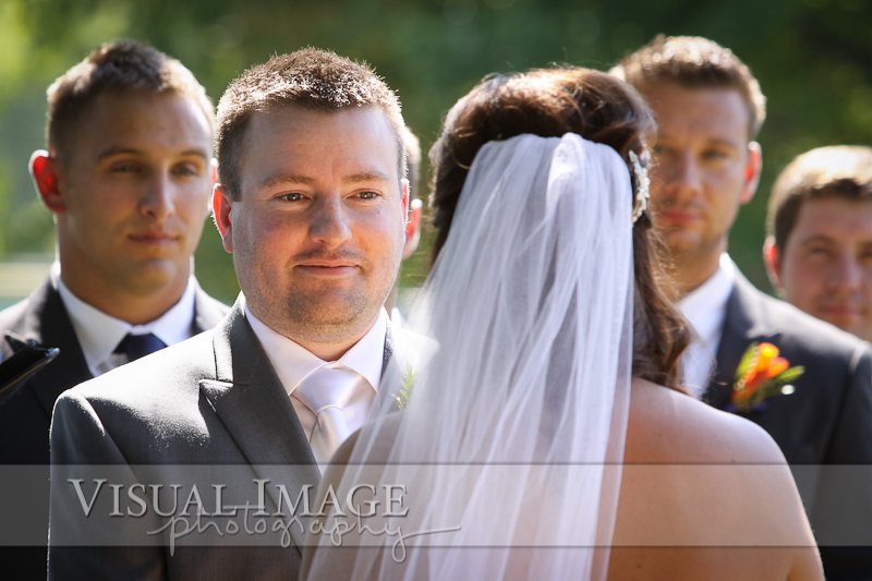 Groom looking at bride during wedding ceremony in Frame Park