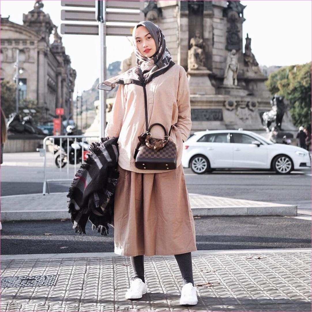 Outfit Rok Untuk Hijabers Ala Selebgram 2018 top blouse kemeja krem muda stocking hitam slingbags hijab square bermotif coklat tua sneakers kets putih ciput rajut syall rok A-line skirt krem ootd trendy