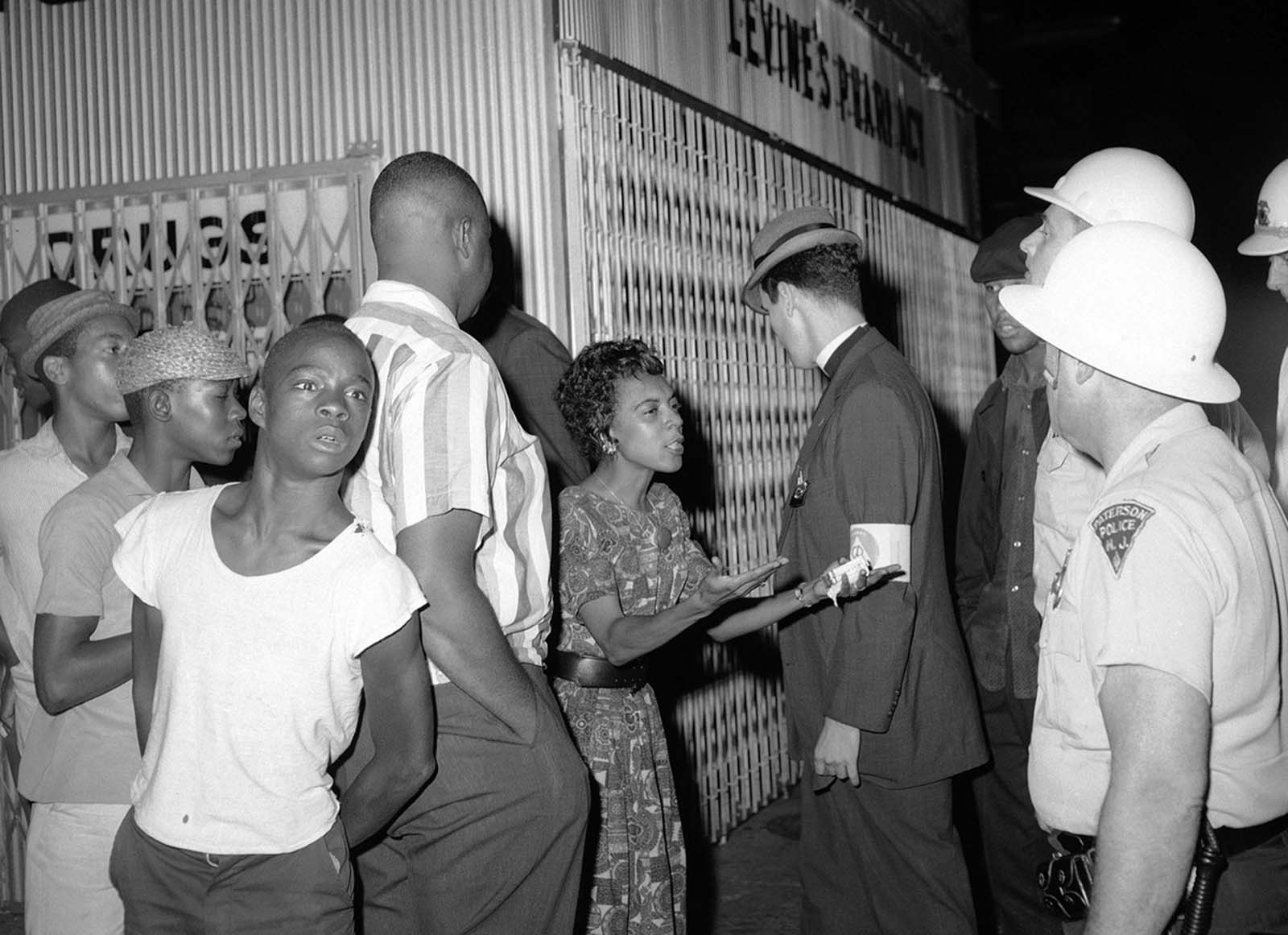 An unidentified woman argues with a policeman in Paterson, New Jersey, on August 12, 1964 while a clergyman, center, tries to intervene.
