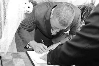K'Mich Weddings - wedding planning - groom signing book