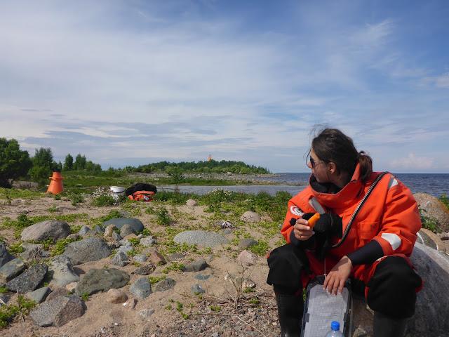 Pelastautumispukuinen henkilö kivellä istumassa syömässä eväitä rannalla
