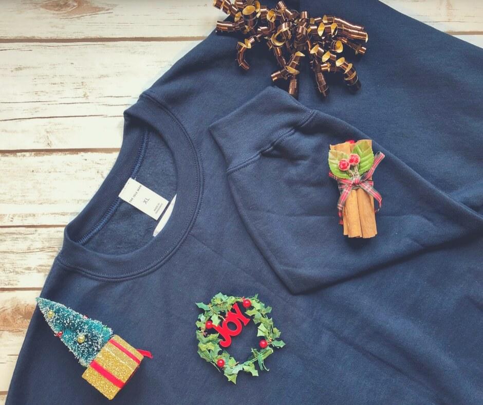 Navy sweatshirt, with fleece feeling inside, with a christmas wreath on the front of it.
