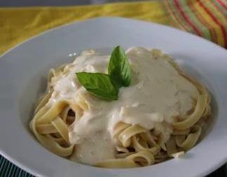 Foto de um prato com a receita de macarrão pronta para consumo, enfeitada com folha de manjericão junto com molho branco.