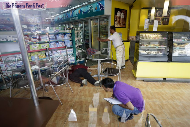 Bystanders examine the body of political activist Kem Ley after he was fatally shot by a gunman by a CalTex service station in Phnom Penh this morning. Hong Menea