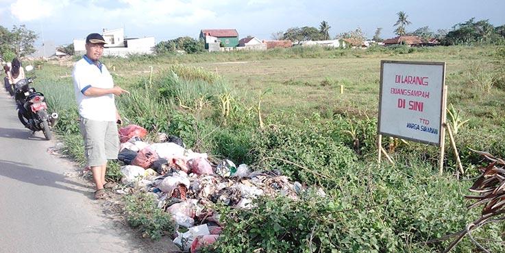 Sampah menumpuk dipinggir jalan, padahal ada plang larangan.