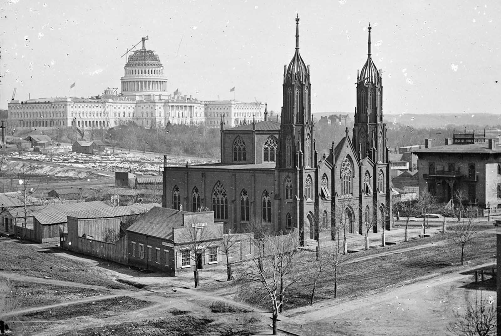 A view of Washington, District of Columbia, from the intersection of 3rd and Indiana Avenue, ca. 1863. In the foreground is Trinity Episcopal Church, in the background, the unfinished Capitol building. Construction on the capitol was briefly suspended early in the war, but continued through the later years.