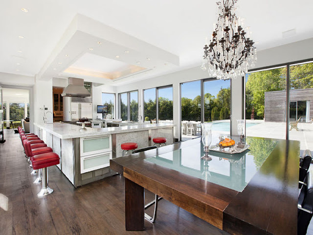 Open kitchen with red stools, wood floor, marble island counter tops, a wood table, chandelier and large windows overlooking a backyard with a pool