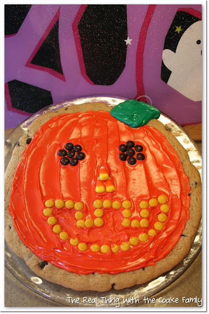 chocolate chip cookie decorated like a pumpkin on a plate