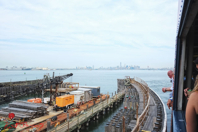Dockside works at Staten Island ferry terminal with a distant view of the Manhattan skyline.  Travel photography by Kent Johnson.