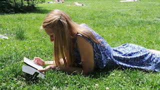 在屋外陽光下用電子書閲讀器讀書