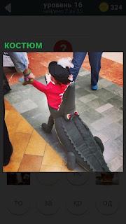 В помещении идет ребенок одетый в костюм крокодила с хвостом