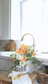 roses in farmhouse sink in kitchen