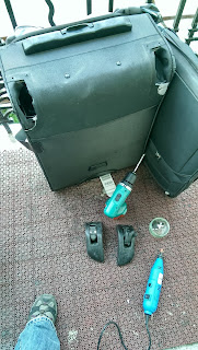 Removing wheels of a suitcase with a drill
