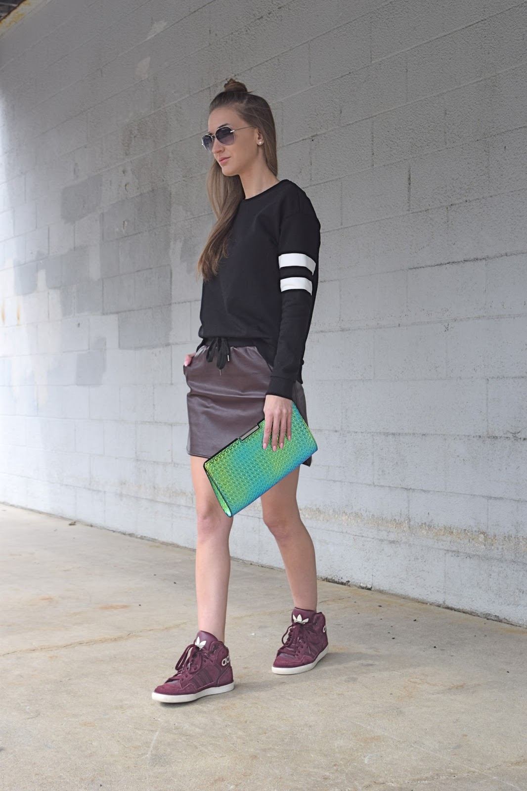 wearing a sporty chic casual look. Wearing adidas sneakers with skirt. Half bun look