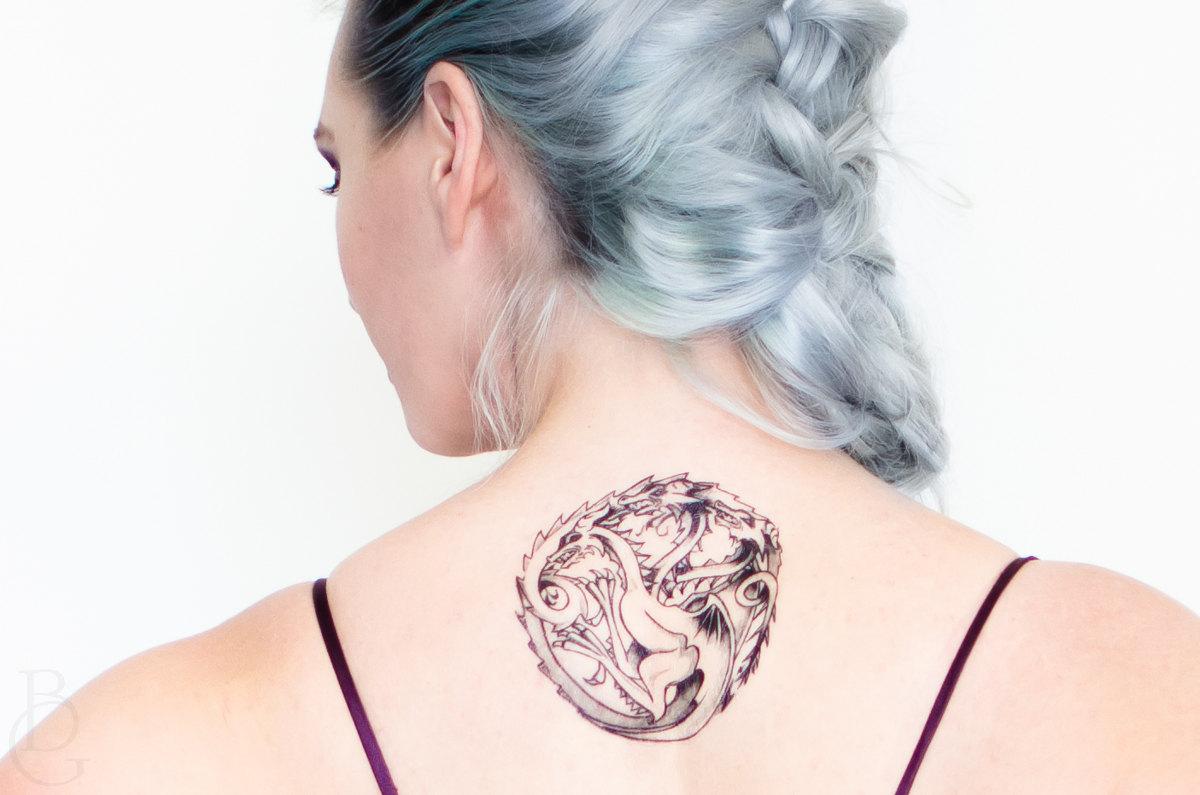 Chica con tatuaje de la casa Targaryen en la espalda